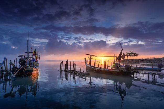Bella spiaggia con la barca del pescatore durante l'alba. Foto Premium