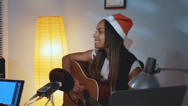 Bella donna di colore in cappello della santa cantando e suonando la chitarra alla vigilia di natale Foto Premium