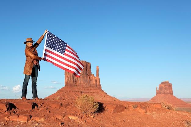 Bella donna bionda che tiene la bandiera usa alla monument valley Foto Premium