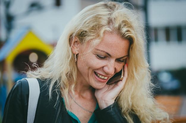 Bella ragazza bionda con i capelli ricci parlando su uno smartphone in una strada cittadina. il lavoro di un libero professionista, la decisione di momenti di lavoro. Foto Premium