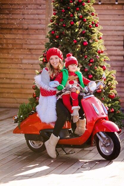 Bella mamma bionda e figlio in maglioni rossi di natale e cappelli rossi si siedono su un ciclomotore vintage rosso sullo sfondo di un albero di natale sotto la neve volante. foto di alta qualità Foto Premium