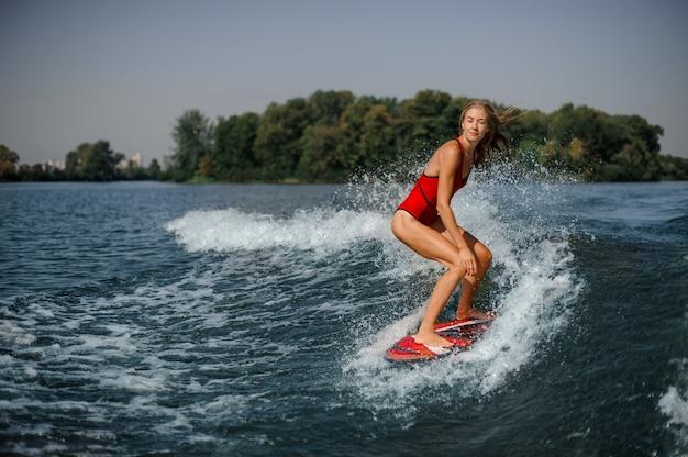 Bello surfista biondo della donna che guida giù l'onda di spruzzatura blu Foto Premium