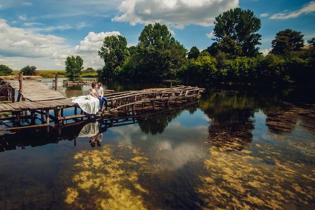 Bella sposa e sposo in posa su un ponte Foto Premium