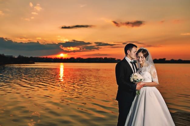 Bella sposa e sposo in posa vicino al lago al tramonto Foto Premium