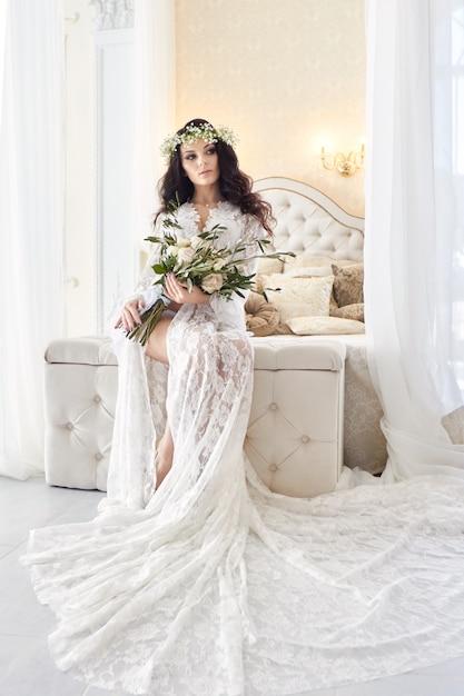 Bella sposa in lingerie e con una corona di fiori in testa, la mattina prima del matrimonio. vestaglia bianca della sposa, preparando per la cerimonia nuziale. ragazza sexy sul letto Foto Premium