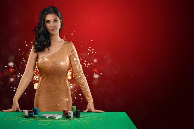 Una bella ragazza castana con un vestito da croupier lucido dorato si trova davanti a un tavolo da gioco Foto Premium