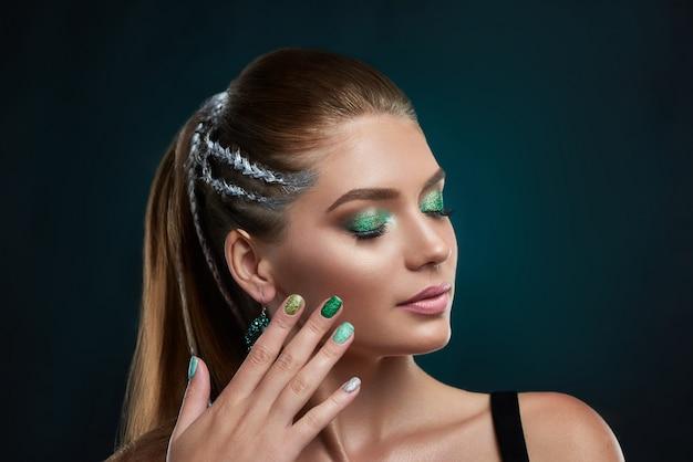 Bella ragazza castana con l'acconciatura alla moda con elementi di trucco brillante argento e verde in posa. donna che tocca il viso a mano, mostrando una perfetta manicure. concetto di bellezza. Foto Premium