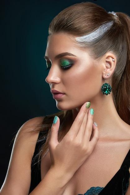 Bella donna castana con l'acconciatura con elementi di trucco lucido argento e verde Foto Premium