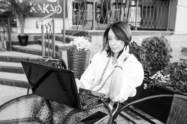 Bella donna d'affari che si siede nel caffè della città e lavora con il suo computer portatile. immagine in bianco e nero Foto Premium