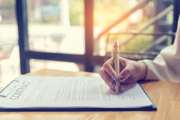 Bella donna d'affari utilizzando la penna firma il nuovo contratto per l'avvio di progetti. donna lavoratrice lavoro all'aperto. concetti di business. Foto Premium