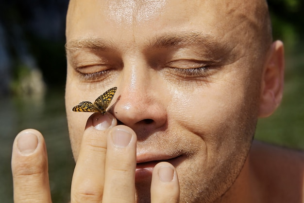 Bella farfalla è seduta sul naso di un allegro uomo senza peli, lo sta toccando con le dita. Foto Premium