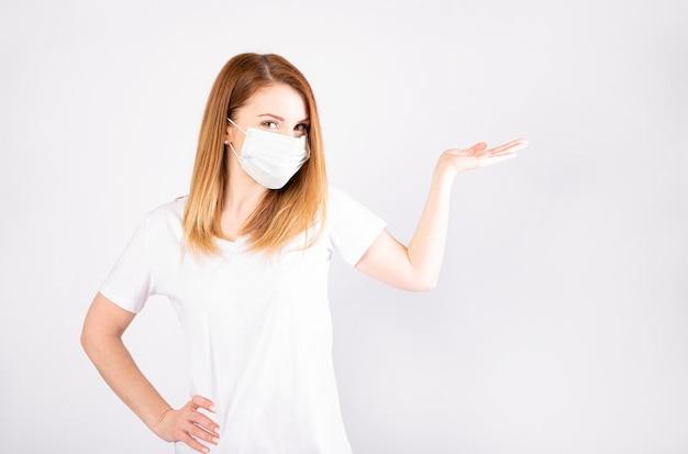 Bella giovane donna caucasica in maglietta bianca con maschera usa e getta. protezione contro virus e infezioni. Foto Premium