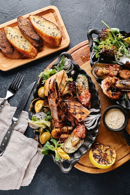 Bellissima composizione su un tavolo di pesce servito, calamari, gamberi, trancio di salmone e polpo. Foto Premium