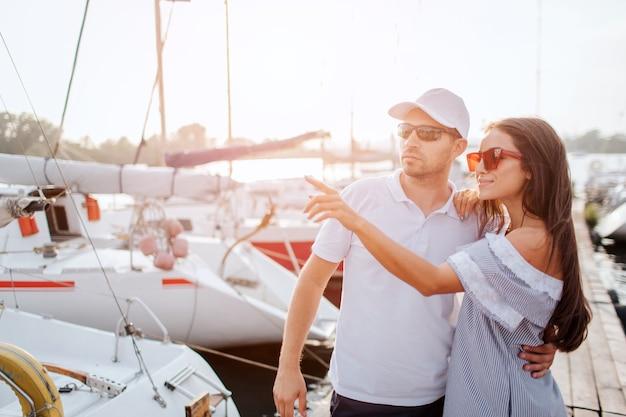 Coppia bella e sicura di sé si leva in piedi sul molo e si abbracciano. sono molto vicini. punto della ragazza con il dito Foto Premium