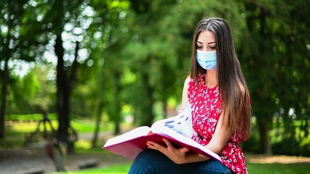 Bello studente di college femminile che legge un libro su un banco in un parco e che indossa una maschera nei periodi di coronavirus Foto Premium