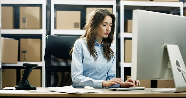 Bella lavoratrice postale che lavora al computer nell'ufficio di consegna postale e che scrive sulla tastiera. Foto Premium
