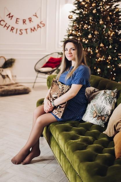Bella donna si siede sul divano vicino all'albero di natale Foto Premium