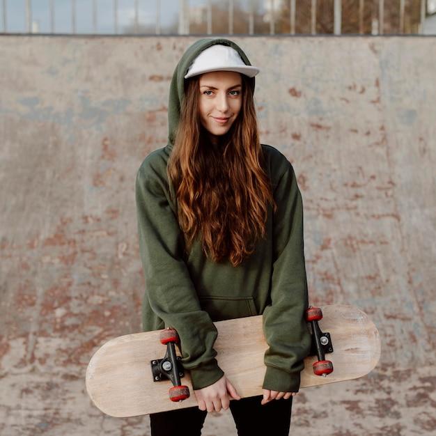 Bello pattinatore femminile che tiene la sua vista frontale dello skateboard Foto Premium