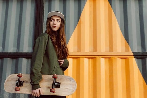 Bello pattinatore femminile che tiene il suo skateboard Foto Premium
