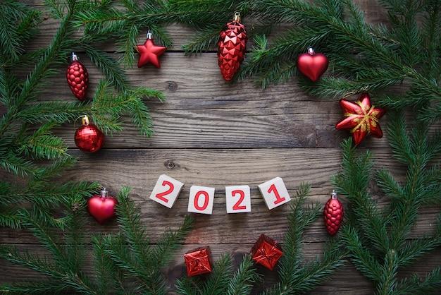 Bella cornice di rami di albero di natale con giocattoli e numero 2021. felice anno nuovo sfondo Foto Premium