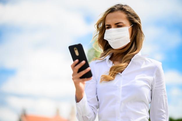 Bella ragazza da sola giovane donna che utilizza il suo smartphone e indossa una maschera, concetto di coronavirus Foto Premium