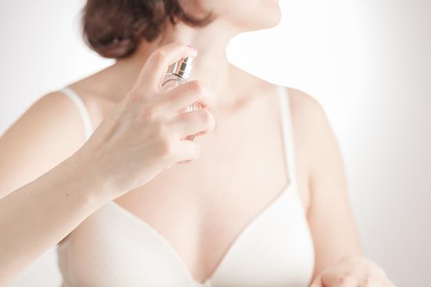 La bella ragazza in telo da bagno sta usando il profumo Foto Premium