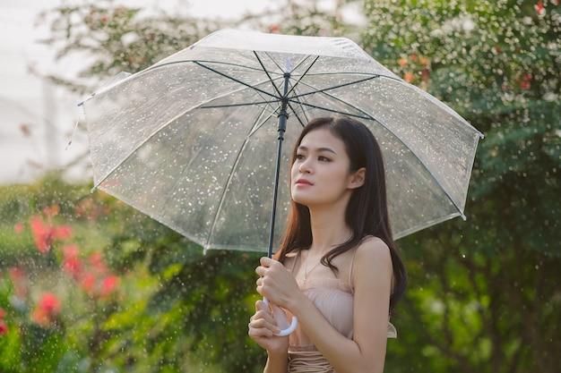 Bella ragazza con ombrello mentre si cammina nel parco Foto Premium