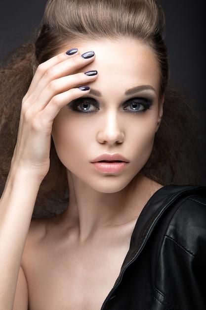 Bella ragazza in giacca di pelle con trucco luminoso e manicure cat's eye. Foto Premium