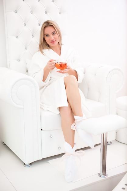 La bella ragazza si rilassa in un accappatoio bianco con una tazza di tè tra le mani nello spasalone. Foto Premium