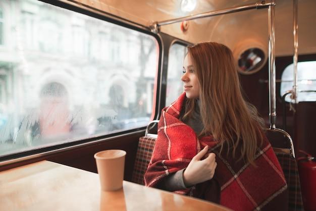 La bella ragazza si siede in un'accogliente caffetteria e calorosamente coperta con una coperta Foto Premium