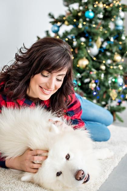 Bella ragazza con i riccioli in una camicia a quadri rossi ride e abbraccia un husky samoiedo che si lecca sulla guancia Foto Premium