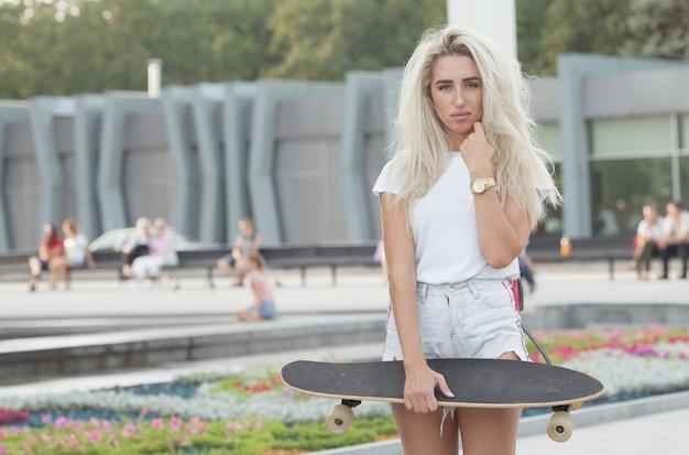 Bella ragazza con lo skateboard. ragazza che tiene uno skateboard in mano. Foto Premium