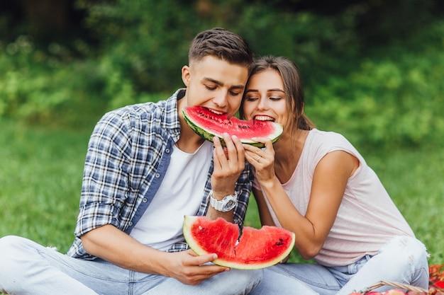 Belle giovani coppie in buona salute con cibo sano. anguria ed estate. Foto Premium