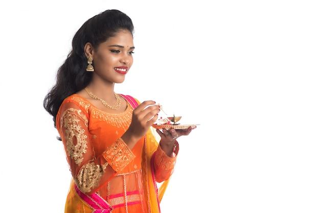 Thali indiano di pooja della tenuta della bella ragazza o culto di esecuzione su una parete bianca Foto Premium