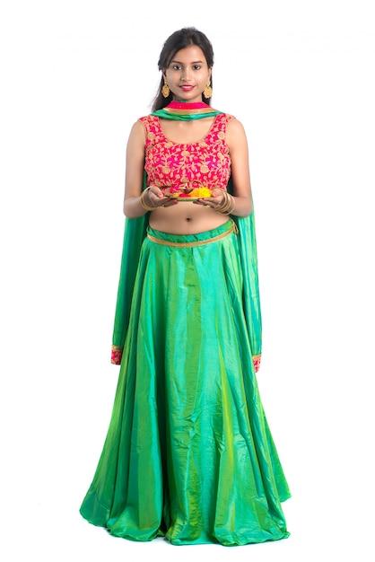 Thali indiano bello di pooja della tenuta della ragazza o culto di esecuzione su un bianco Foto Premium