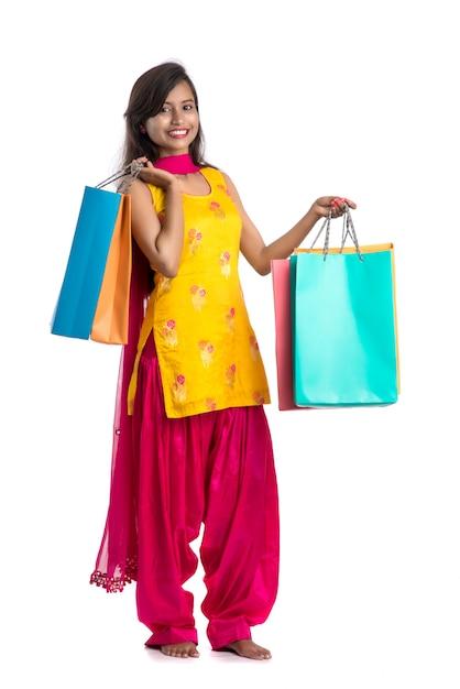 Bella ragazza indiana che tiene e che posa con i sacchetti della spesa su uno spazio bianco Foto Premium