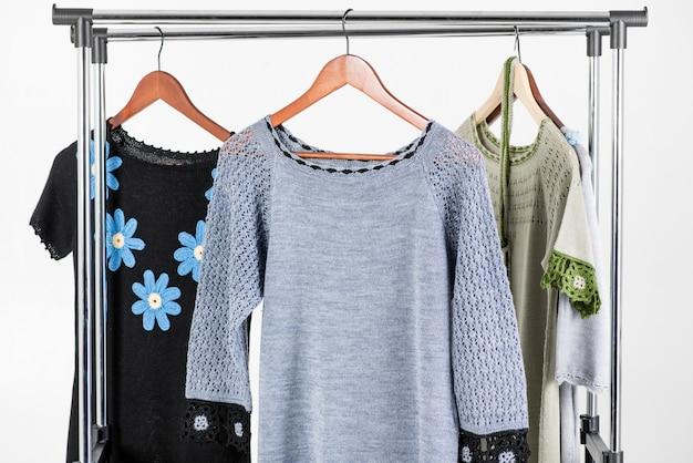 Bella abiti lavorati a maglia appesi su un appendiabiti su uno sfondo chiaro Foto Premium