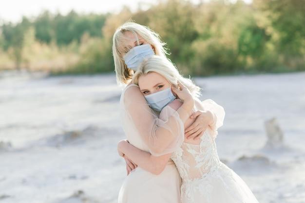 Belle coppie lesbiche che camminano sulla sabbia lungo una riva del fiume il giorno delle nozze Foto Premium