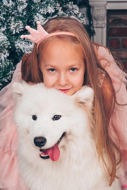 La bella bambina bionda sta sorridendo con un cane samoiedo divertente bianco Foto Premium