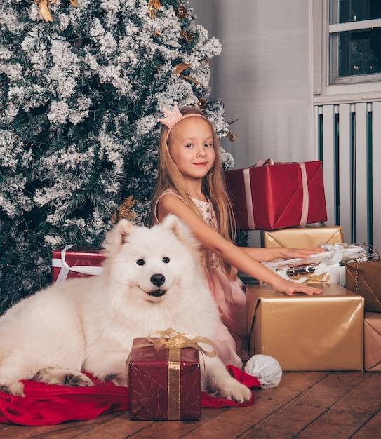Bella piccola principessa bionda ragazza sorride con un divertente cane bianco samoiedo dall'albero di capodanno con scatole regalo. Foto Premium