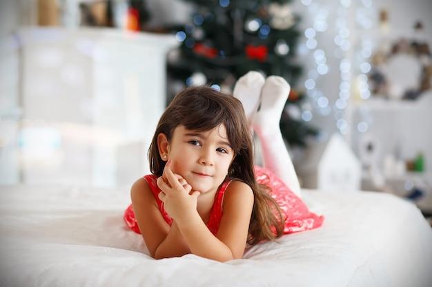 Bella piccola ragazza castana che aspetta un miracolo nelle decorazioni di natale Foto Premium