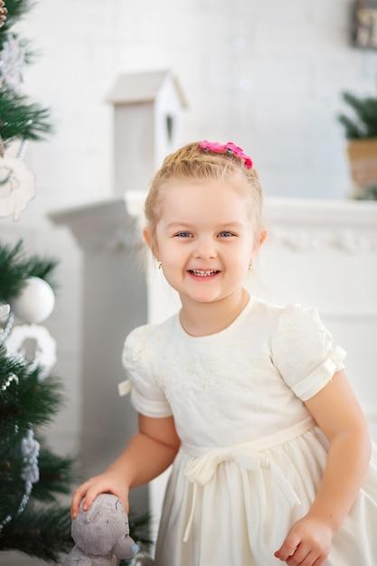 Bella bambina in attesa di un miracolo nelle decorazioni natalizie Foto Premium