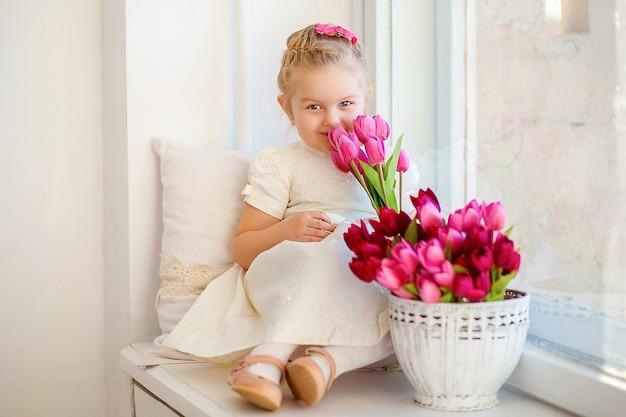 Bella bambina in un vestito bianco che si siede su un davanzale con un mazzo di tulipani rosa Foto Premium