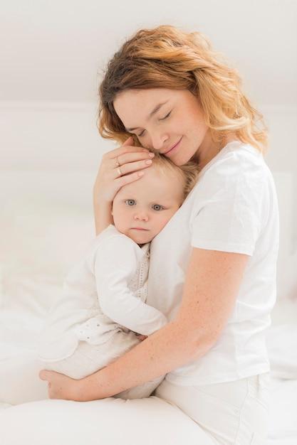 Bella madre che tiene la sua bambina Foto Premium