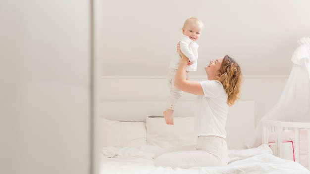 Bella madre che gioca con il suo bambino Foto Premium