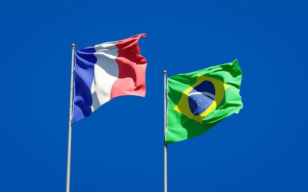 Belle bandiere di stato nazionali di francia e brasile insieme sul cielo blu Foto Premium