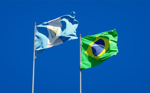 Belle bandiere nazionali dello stato del guatemala e del brasile insieme sul cielo blu Foto Premium