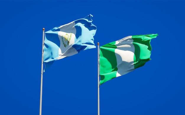 Belle bandiere di stato nazionali del guatemala e della nigeria insieme sul cielo blu Foto Premium