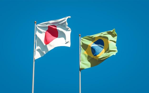 Belle bandiere di stato nazionali del giappone e del brasile insieme sul cielo blu Foto Premium