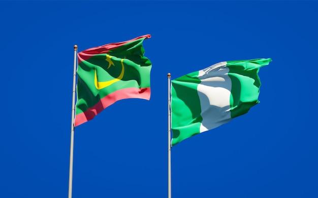 Belle bandiere di stato nazionali della mauritania e della nigeria insieme sul cielo blu Foto Premium